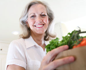 Senior Woman Holding Grocery Bag Full of Vegetables
