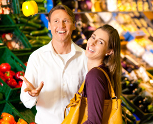 Couple laughing in produce aisle