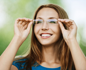 Smiling woman putting on glasses