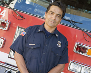 Man in uniform standing in front of firetruck