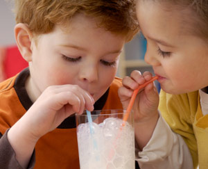 Two children sharing milk